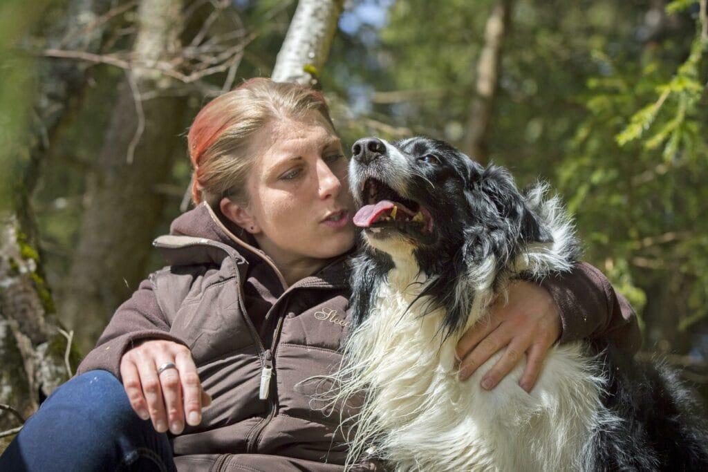 Hundebesitzerin und Ihr Hund im Wald: wann ist der richtige Zeitpunkt eine Hündin zu kastieren?